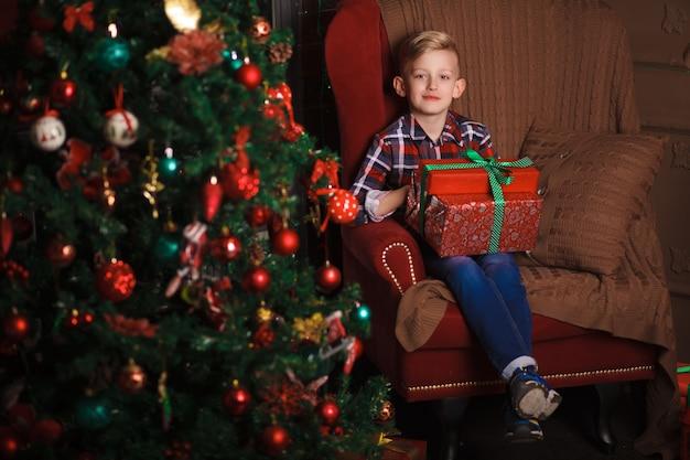Beau petit garçon est assis sur une chaise avec des cadeaux près de l'arbre de noël.