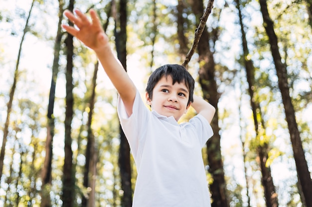 Beau petit garçon jouant avec un bâton en plein air