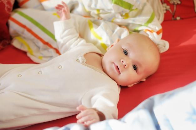 Beau petit garçon joue au lit