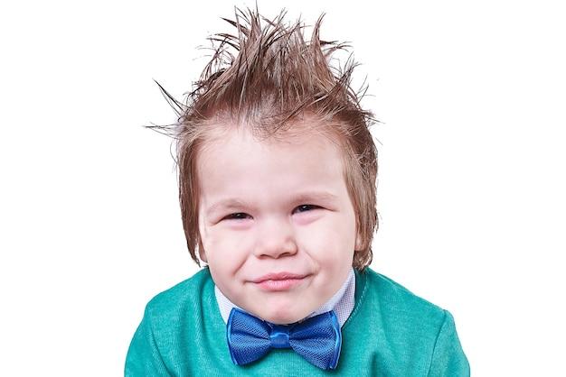 Beau petit garçon en noeud papillon bleu et pull vert et elle fait des grimaces isolées
