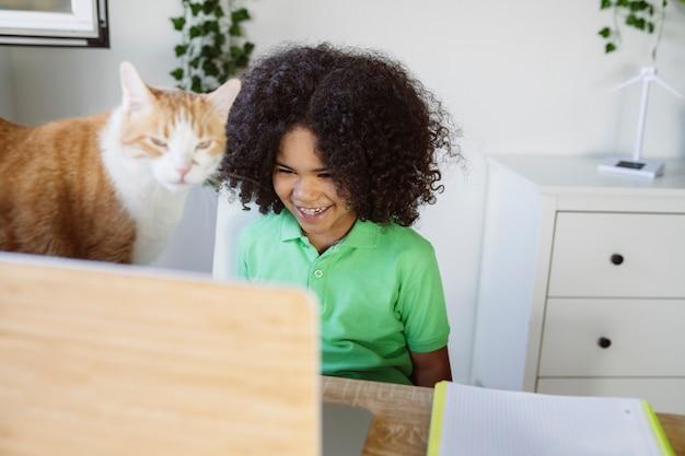 Beau petit garçon avec ordinateur et chat à la maison