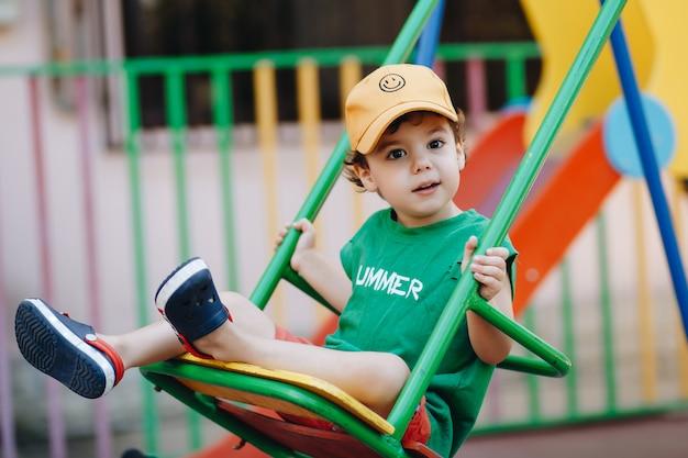 Beau petit garçon tournant sur une balançoire d'été avec un espace pour le texte
