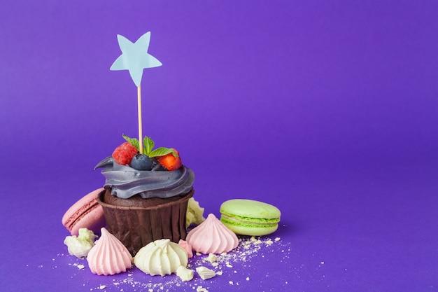 Beau petit gâteau sur fond violet foncé saturé
