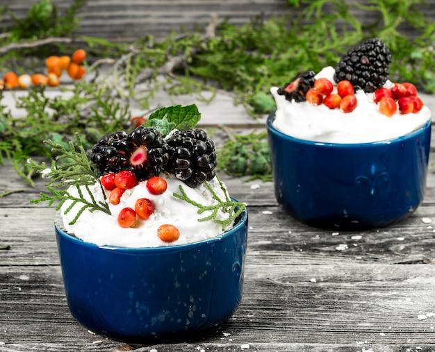 Beau petit gâteau de noël avec de la crème et des baies sur des cônes de cannelle mur en bois