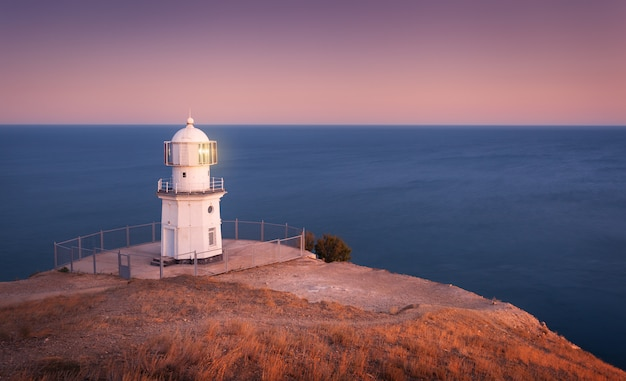 Beau phare blanc sur la côte de l'océan au coucher du soleil