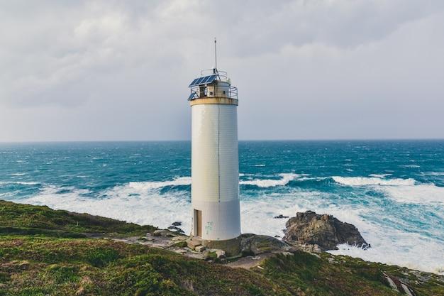 Beau phare dans les falaises avec la magnifique mer orageuse