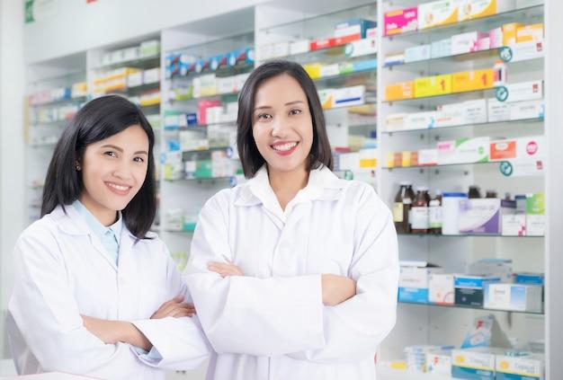 Beau pharmacien souriant jeune femme fait son travail en pharmacie.