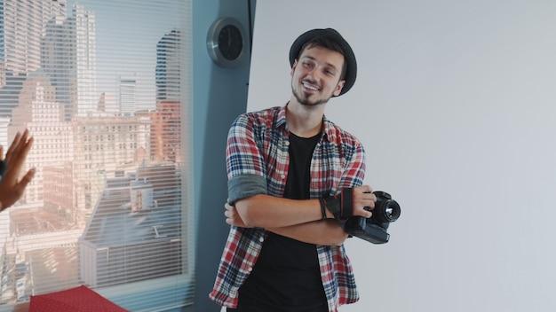 Beau photographe posant pour quelqu'un qui prend des photos avec smartphone