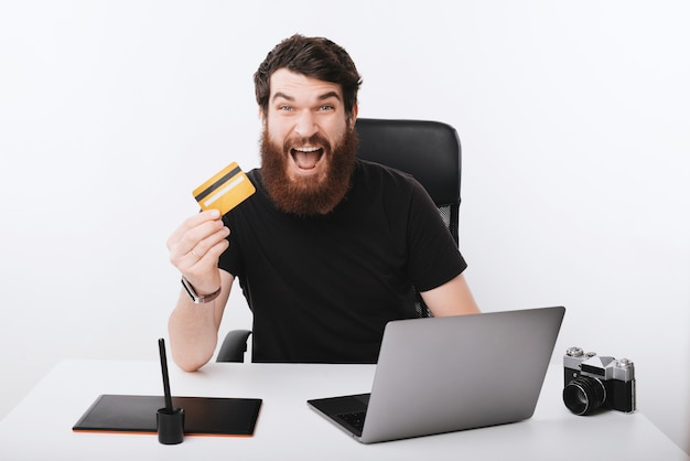 Un beau pigiste barbu excité, l'air excité à la caméra et montrant sa carte de crédit