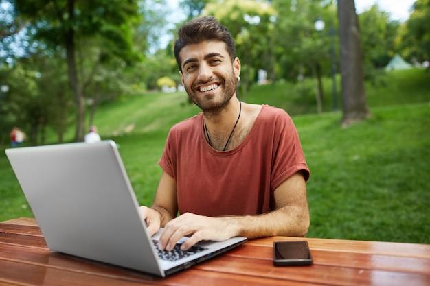 Beau pigiste travaillant à distance, asseyez-vous sur un banc de parc avec ordinateur portable, connectez le wifi