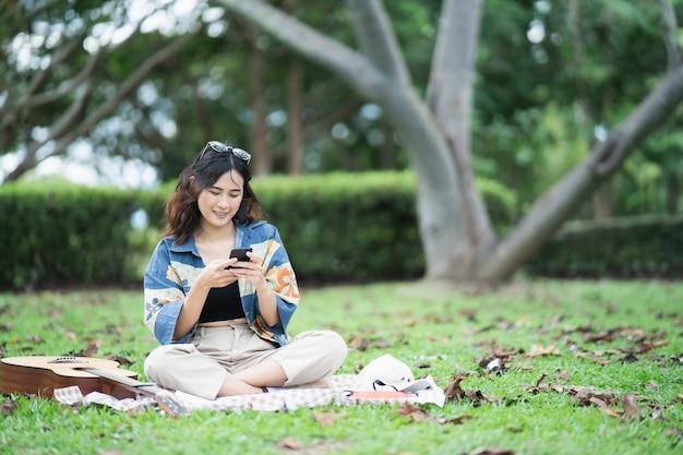 Beau pique-nique étudiant asiatique dans le parc et penser à composer une chanson