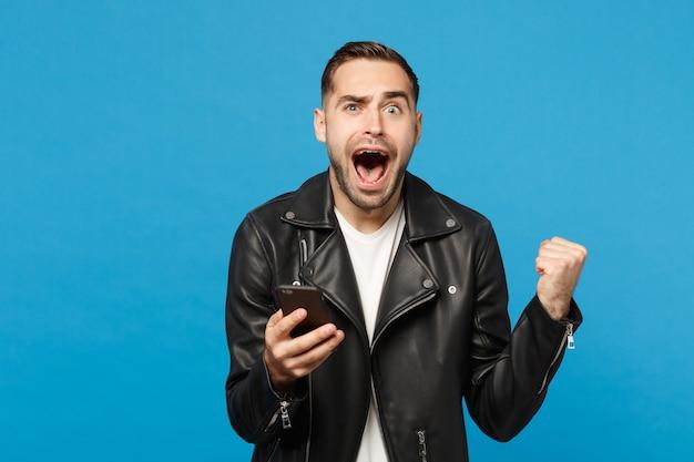 Beau plaisir ravi excité jeune homme mal rasé en t-shirt blanc veste en cuir noir à l'aide d'un téléphone portable isolé sur fond de mur bleu portrait en studio. concept de mode de vie des gens mock up copy space