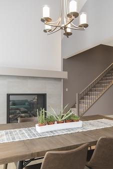 Beau plan d'une salle à manger de maison moderne avec des plantes et une cheminée