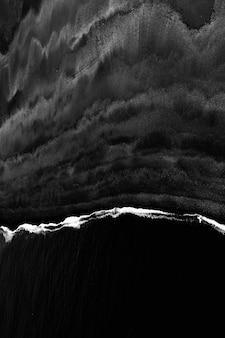 Beau plan vertical en niveaux de gris des vagues de la mer