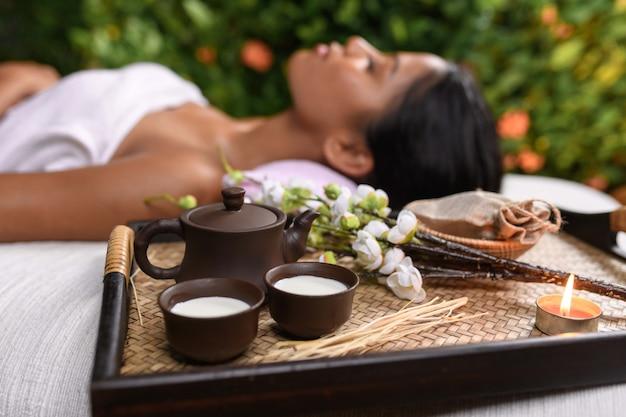 Un beau plateau avec des huiles aromatiques et un brin de fleurs blanches avec des bougies et une théière en argile et deux chopes en argile. fille se trouve dans une serviette