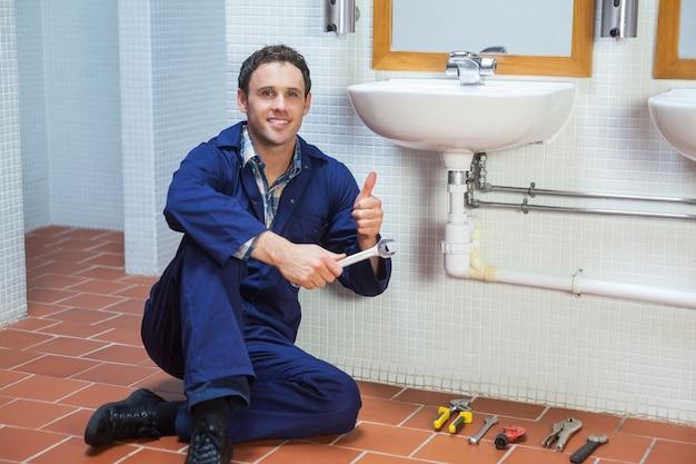 Beau plombier heureux assis à côté de l'évier montrant le pouce vers le haut