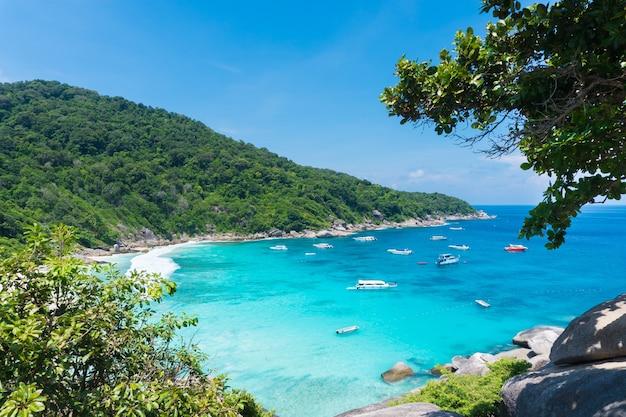 Beau point de vue avec ciel bleu et nuages, mer bleue et plage de sable blanc avec bateau