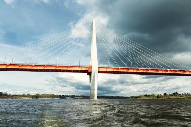 Un beau pont à haubans au-dessus de la rivière sur fond de ciel nuageux sombre. beau paysage.