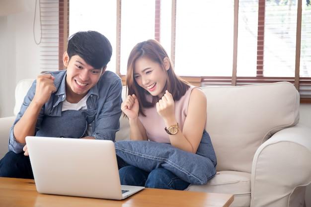 Beau portrait asiatique jeune couple travaillant sur un ordinateur portable