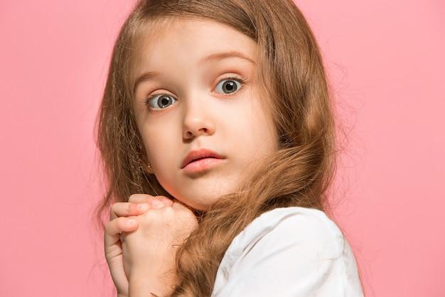 Beau portrait avant féminin isolé sur fond de studio rose. jeune adolescente surprise émotionnelle.