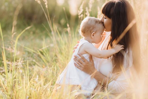 Beau portrait de charmante mère et jolie petite fille marchant à travers le champ