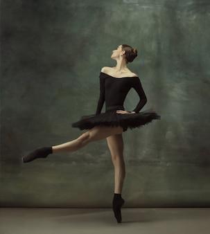 Beau portrait. danse de ballerine classique gracieuse, posant isolé sur fond de studio sombre. tutu noir élégance. concept de grâce, de mouvement, d'action et de mouvement. semble en apesanteur. à la mode.
