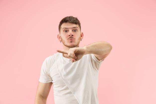 Beau portrait de demi-longueur mâle isolé sur fond de studio rose. le jeune émotionnel surpris