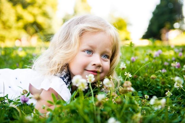 Beau portrait d'été de petite fille dans l'herbe