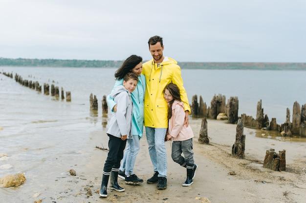 Beau portrait de famille vêtu d'un imperméable coloré près du lac