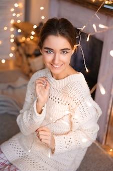 Beau portrait féminin d'une jeune fille dans un pull blanc sur fond de guirlandes et de bokeh. ambiance festive confortable