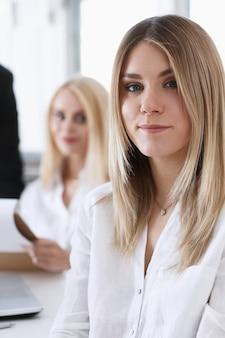 Beau portrait de femme d'affaires souriant au lieu de travail à la recherche directe