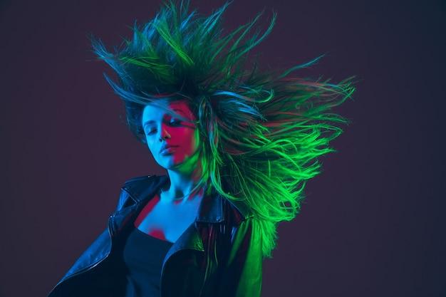 Beau portrait de femme avec des cheveux volants sur fond de studio sombre en vert coloré