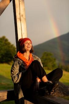 Beau portrait de femme à côté d'un arc-en-ciel