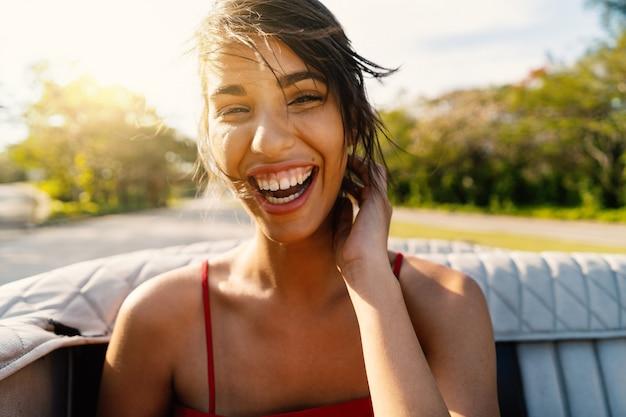 Beau portrait de femme cubaine qui rit sur une voiture cabriolet vintage à cuba. image de style de vie réelle dans une journée ensoleillée avec des reflets flare.