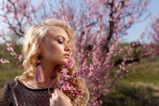 Beau portrait d'une femme dans un jardin de pêches en fleurs