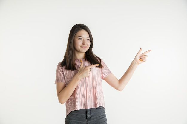 Beau portrait de femme demi-longueur isolé sur fond de studio blanc. jeune femme émotionnelle dans des vêtements décontractés. émotions humaines, concept d'expression faciale. pointant sur le côté, souriant.