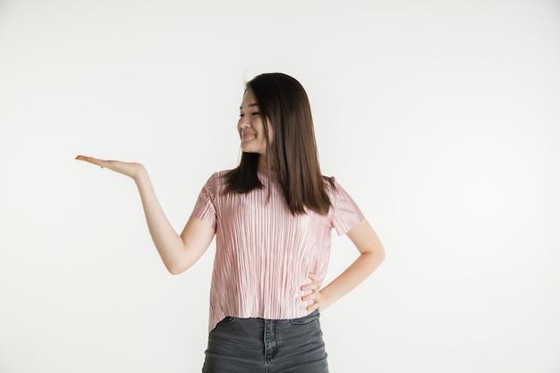Beau portrait de femme demi-longueur isolé sur fond de studio blanc. jeune femme émotionnelle dans des vêtements décontractés. émotions humaines, concept d'expression faciale. tient et montre copyspace, sourit.