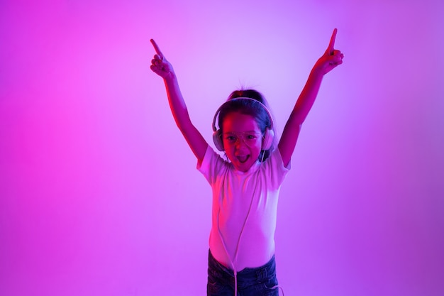 Beau portrait de femme demi-longueur isolé sur fond violet en néon. jeune adolescente émotionnelle à lunettes. émotions humaines, concept d'expression faciale. couleurs à la mode. danser, pointer.