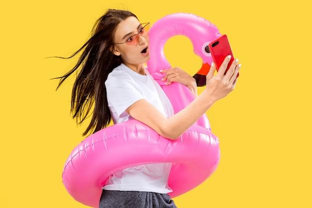 Beau portrait de femme demi-longueur isolé sur mur jaune. jeune femme souriante à lunettes de soleil rouges faisant selfie. expression faciale, été, week-end, concept de villégiature. couleurs à la mode.