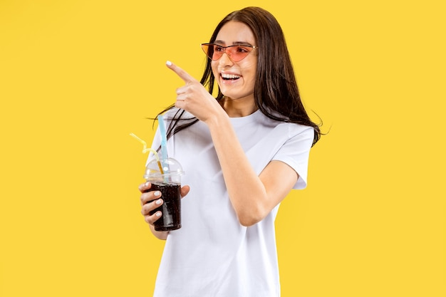 Beau portrait de femme demi-longueur sur studio jaune