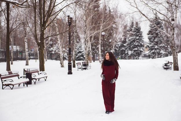 Un beau portrait de femme enceinte dans un parc enneigé
