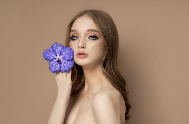Beau portrait de femme avec une orchidée vanda bleue