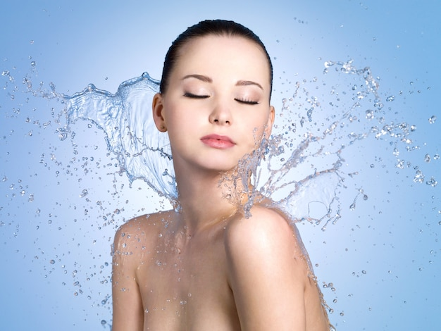 Beau portrait de femme à la peau fraîche dans les éclaboussures d'eau - espace bleu