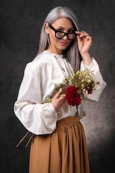 Beau portrait de femme senior avec des fleurs