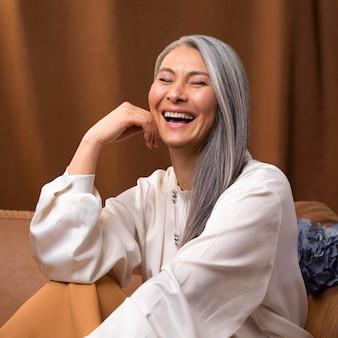 Beau portrait de femme senior posant sur canapé