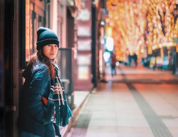 Beau portrait de femme en vêtements d'hiver dans la nuit dans le festival des lumières de noël jozenji à sendai, japon