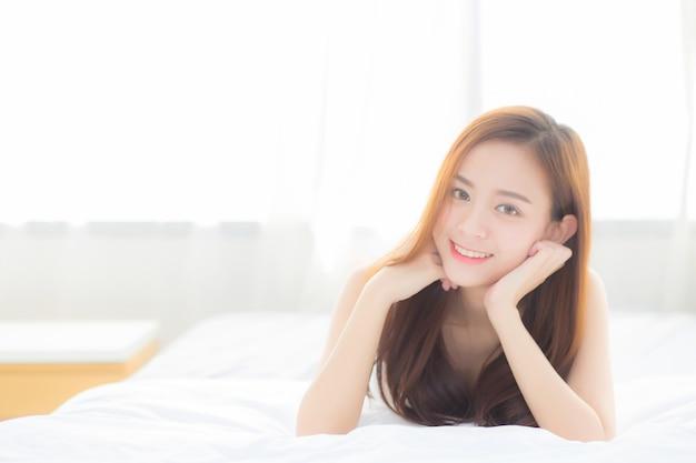 Beau portrait jeune femme asiatique mentir et sourire tout en se réveillant avec le lever du soleil