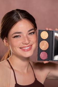 Beau portrait de jeune femme avec un produit de maquillage