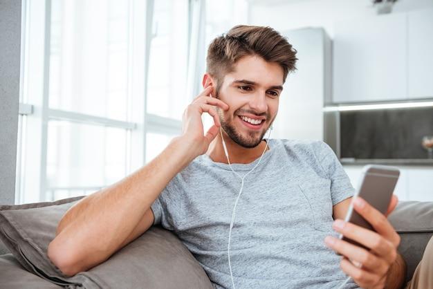 Beau portrait de jeune homme écoutant de la musique tout en se trouvant sur le canapé et bavardant.