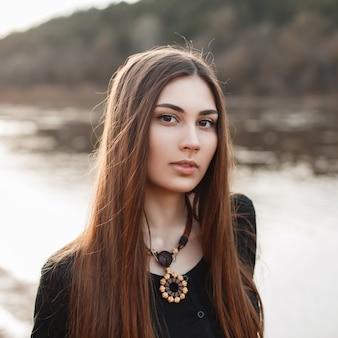 Beau portrait d'une jeune jolie fille aux cheveux longs près de l'eau